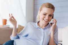 Pregnant woman talking on a cellphone in her room Stock Image