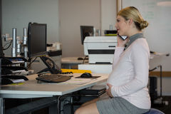 Pregnant woman talking on mobile phone at desk Stock Image
