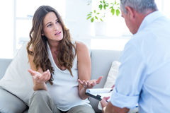 Pregnant woman talking with psychiatrist Stock Photo