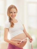 Pregnant woman with tape measuring her belly Stock Image
