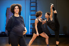 Pregnant woman teaching dance to students in theatre. Portrait of pregnant women teaching dance in theater and looking at camera, smiling in backstage Royalty Free Stock Photos