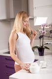 Pregnant woman with teapot in kitchen Royalty Free Stock Images