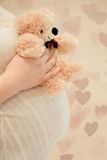 Pregnant woman with teddy bear Stock Photo