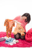 Pregnant woman with teddy bear and children's clothes Stock Photography