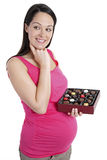 Pregnant woman thinking about chocolates. Pregnant woman deciding whether to have a chocolate Royalty Free Stock Photos