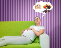 Pregnant woman. Thinking about food. Hungry expectant mother lying on the couch. Egoist concept. Manipulation stock photography