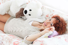Pregnant woman touching her belly while lying on a bed at h Royalty Free Stock Images