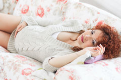 Pregnant woman touching her belly while lying on a bed at h Stock Images