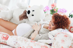 Pregnant woman touching her belly while lying on a bed at h Stock Photography
