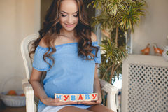 The pregnant woman with toy cubes in hands. Royalty Free Stock Images