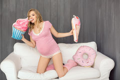 Pregnant woman with toys of ice cream posing indoors at home. Heath care and food consept. Stock Photography