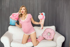 Pregnant woman with toys of ice cream posing indoors at home. Heath care and food consept. Royalty Free Stock Photography