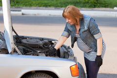 Pregnant Woman Trying to Repair Car Royalty Free Stock Photos