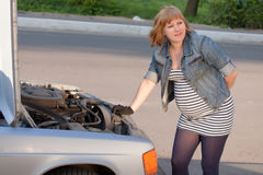 Pregnant Woman Trying to Repair Car Royalty Free Stock Images