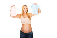 Pregnant woman with two small baby shirts Stock Photography