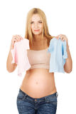 Pregnant woman with two small baby shirts Royalty Free Stock Photo