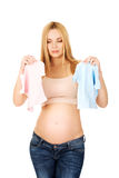Pregnant woman with two small baby shirts Royalty Free Stock Images