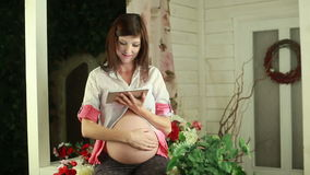 Pregnant woman typing on touch pad. And stroking her tummy stock footage