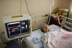Pregnant woman under monitoring. A Chinese pregnant woman laying on hospital bed, under monitoring by machine after giving birth to a child Royalty Free Stock Photography