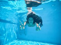Pregnant woman under the water of a pool stock photography