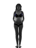 Pregnant woman in underwear  full length silhouette Stock Photos