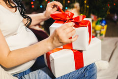 Pregnant woman unpacking christmas box. Red stripe box with hands close up Royalty Free Stock Photos
