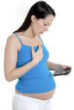 Pregnant woman using calculator Royalty Free Stock Images