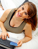 Pregnant woman using credit card to shop from net Stock Images