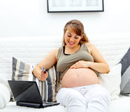 Pregnant woman using credit card to shop from net Stock Image