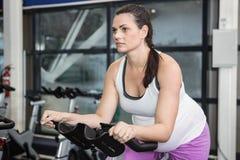 Pregnant woman using exercise bike Royalty Free Stock Image