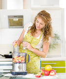 Pregnant woman using a juicer Stock Images