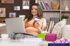 Pregnant woman using laptop. Pregnant woman paying for online shopping by credit card Stock Image