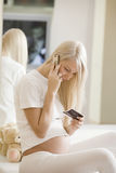 Pregnant Woman Using Mobile Phone. Young pregnant woman using mobile phone on bed Stock Photo