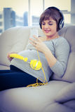 Pregnant woman using smartphone while listening to music. At home Royalty Free Stock Image