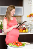 Pregnant woman using a tablet computer in kitchen Stock Photo
