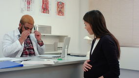 Pregnant woman visiting physician and giving him some medical papers stock footage