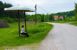 Pregnant woman Waiting for a bus. Young, pregnant woman, sitting near a road in the country side, waiting for a bus on a bus stop Royalty Free Stock Image