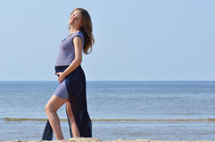 Pregnant woman walking on beach Stock Photo