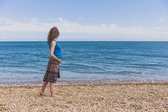 Pregnant woman walking on the beach royalty free stock photo