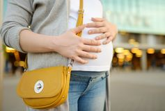 Pregnant woman is walking in the city or make shopping. Maternity leave. Fashion and pregnancy. Urban lifestyle stock photo