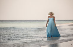 Pregnant woman is walking on the Maldivian beach Royalty Free Stock Photography