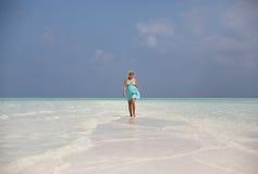 Pregnant woman is walking on sand bank, Maldives Royalty Free Stock Photo