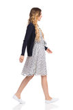 Pregnant Woman Is Walking Side View Isolated. Young pregnant woman in white dotted dress, sneakers and blue cardigan is walking. Side view. Full length studio Royalty Free Stock Photo