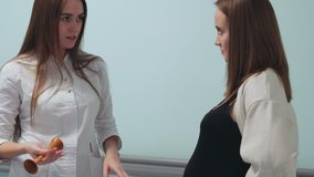 A pregnant woman walks in the corridor of the transplant center communicating with a doctor in a white dressing gown. Preparation for childbirth. child in the stock footage