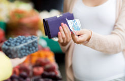 Pregnant woman with wallet buying beries at market Stock Photos