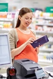 Pregnant woman with wallet at cashbox in drugstore Royalty Free Stock Photos
