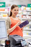 Pregnant woman with wallet at cashbox in drugstore Royalty Free Stock Photography