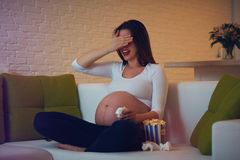 Pregnant woman watching horror movie at home alone Royalty Free Stock Photos