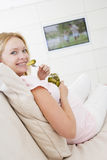 Pregnant woman watching television and eating royalty free stock images