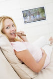 Pregnant woman watching television and eating choc Stock Images